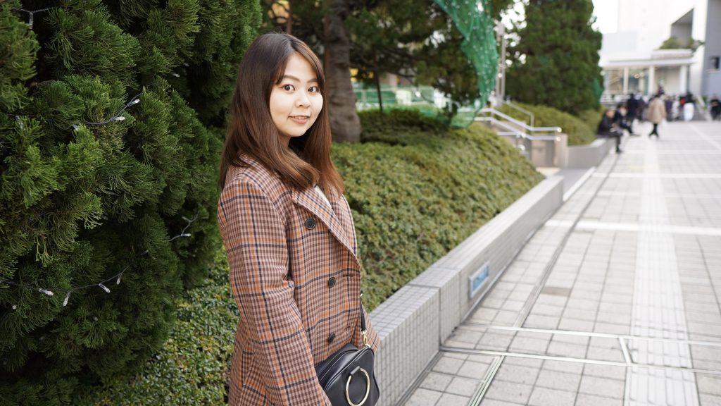 植木のそばで立っている櫻井さんの画像。