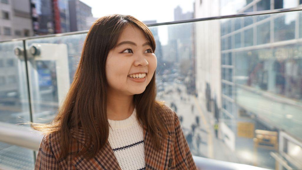 歩道橋の端で、笑顔で斜め前を向いている櫻井さんの画像。
