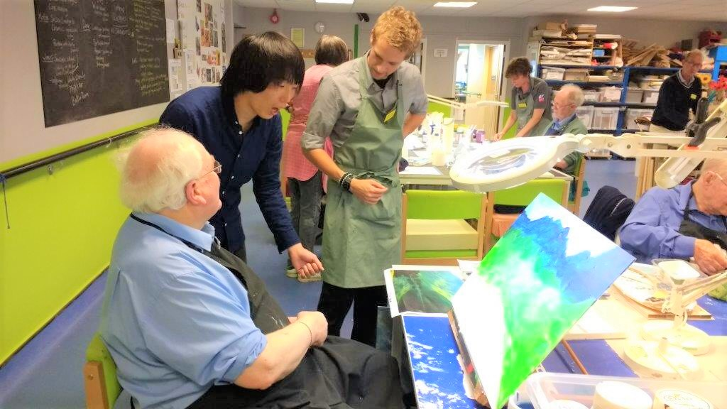 北原さんがイギリスの施設で利用者や職員と風景画を見ながら話をしている画像。