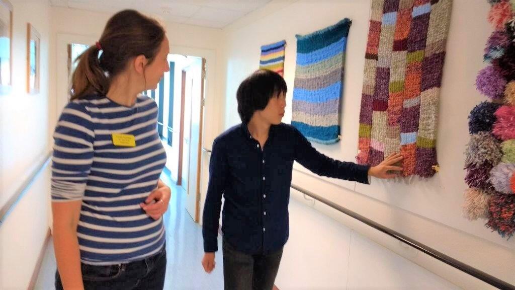 イギリスの施設で廊下の壁にかけられた織物を触る北原さんの画像。