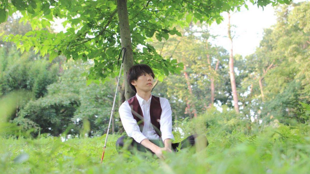 白杖を木に立てかけて芝生の上に座っている北原さんの画像。