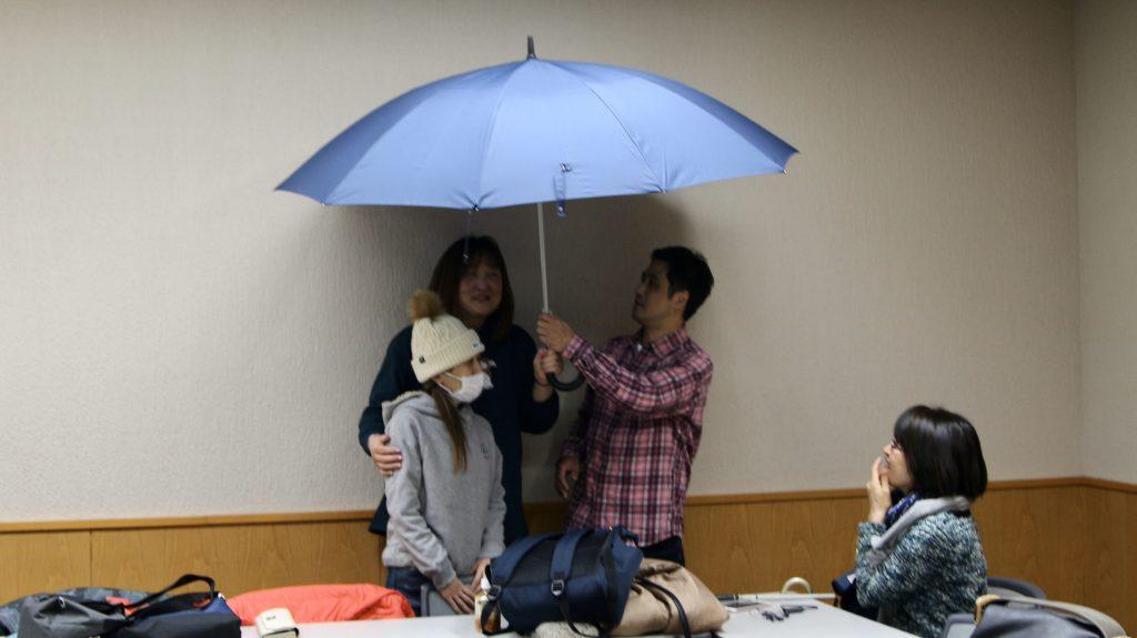 参加者同士で2人用の傘を実際に試している画像。