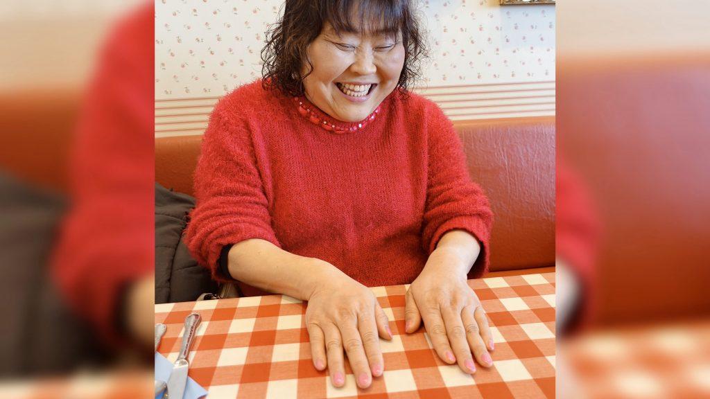 児玉さんが笑顔で自分のネイルを見せている画像。