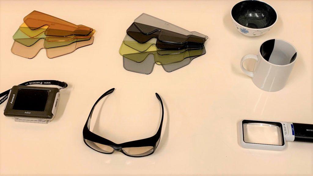遮光眼鏡やルーペ、中身が見やすいマグカップなどの便利グッズを机の上に並べている画像。