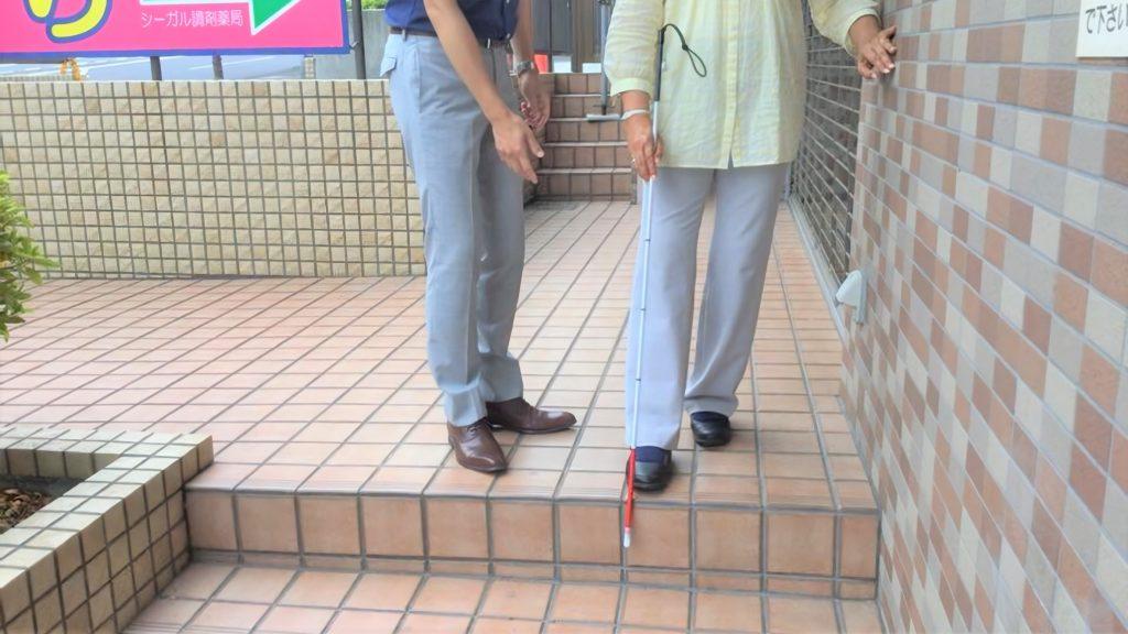 歩行訓練士が患者さんに白杖の操作方法をお伝えしている画像。