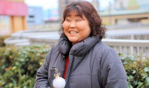 外で立っている笑顔の児玉さんを撮影した画像。