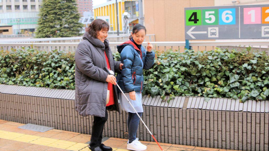 児玉さんがガイドヘルパーと一緒に道路を歩いている画像。