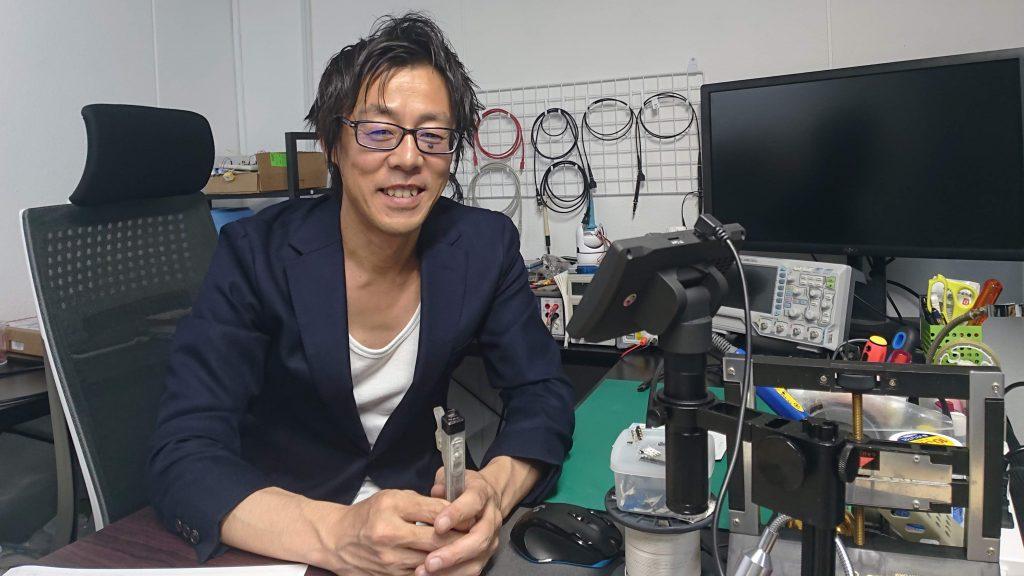中村さんが笑顔でデスクに座っている画像。