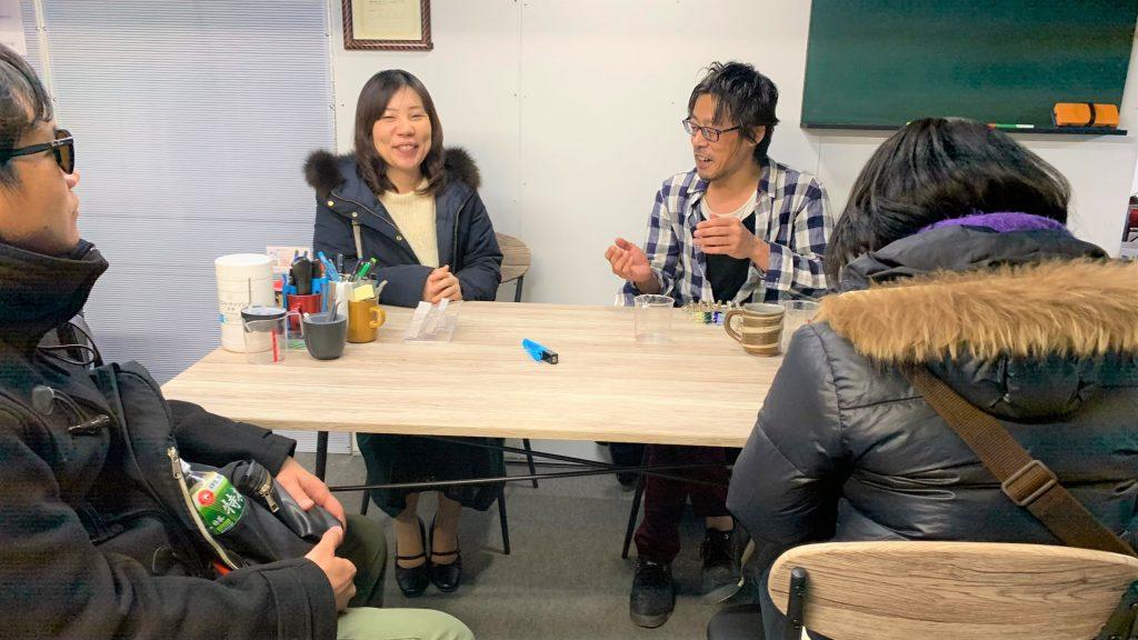 レイズザフラッグの事務所で中村さんが視覚障害者と談笑している画像。