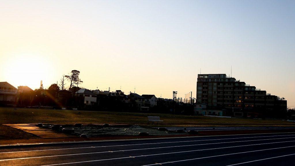 日が沈みかけた陸上競技場の画像。