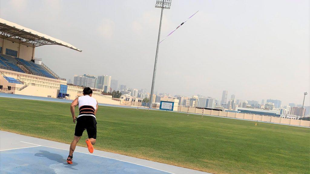 若生選手がドバイの陸上競技場でやりを投げた直後を後ろから撮影した画像。