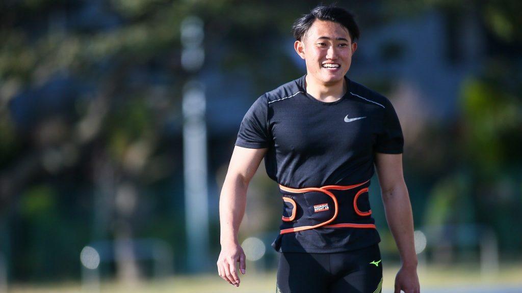 若生選手が陸上競技場を堂々と笑顔で歩いている画像。