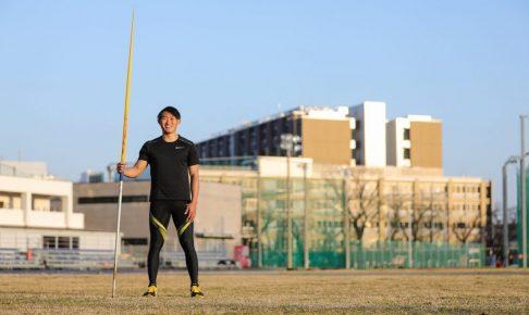 若生選手がやりをもって陸上競技場で立っている画像。