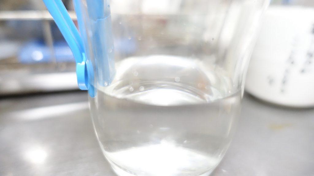 コップに挟んだ水色クリップの先端を撮影した画像。