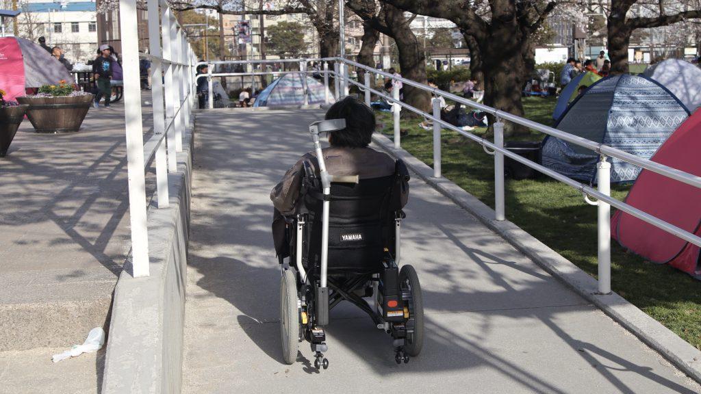 電動車椅子で公園のスロープを登る吉野さんを後ろから撮影した画像。
