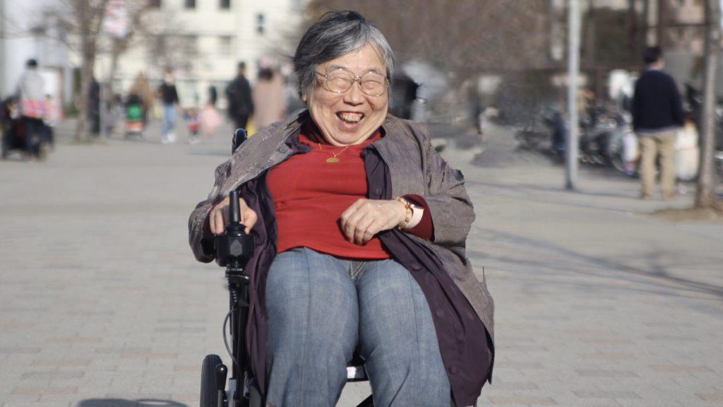 公園の道の真ん中で電動車椅子に乗っている笑顔の吉野さんの画像。