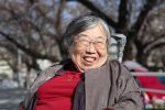 公園の桜の木の下で笑顔の吉野さんを撮影した画像。
