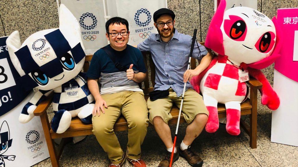 東京オリンピックパラリンピックの撮影スポットで記念撮影するジェッドさんと藤田さんの画像。