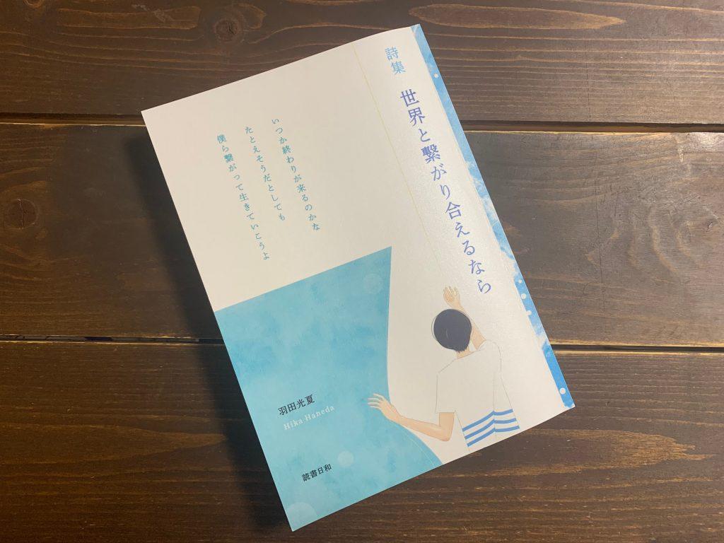 羽田さんの詩集世界と繋がり合えるならを机の上に置いて撮影した画像。