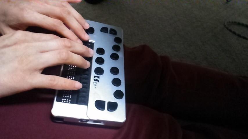 羽田さんがブレイスメモポケットを使って点字を打っている手元の画像。