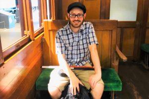 レトロな電車の中で、笑顔で座っているジェッドさんの画像