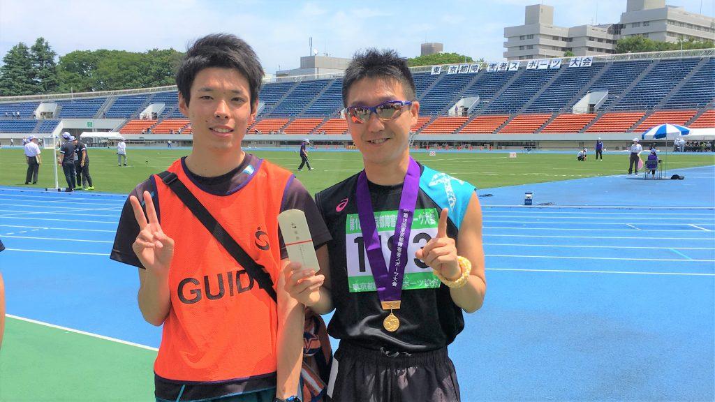 障害者スポーツ大会の表彰式ご、伴走者と一緒に記念撮影する三國さんの画像。