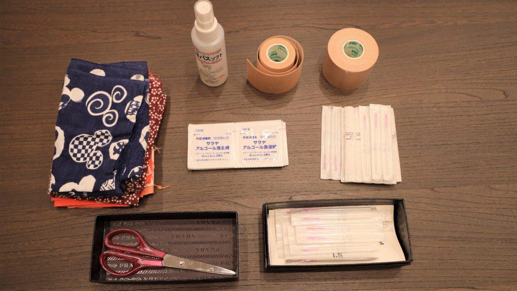 テーピングや針など、マッサージで使用する備品を机の上に並べて撮影した画像。