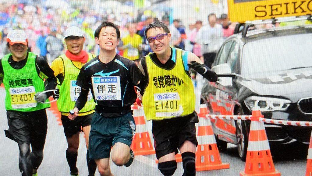 マラソン大会で伴走者と一緒にゴールする三國さんの画像。