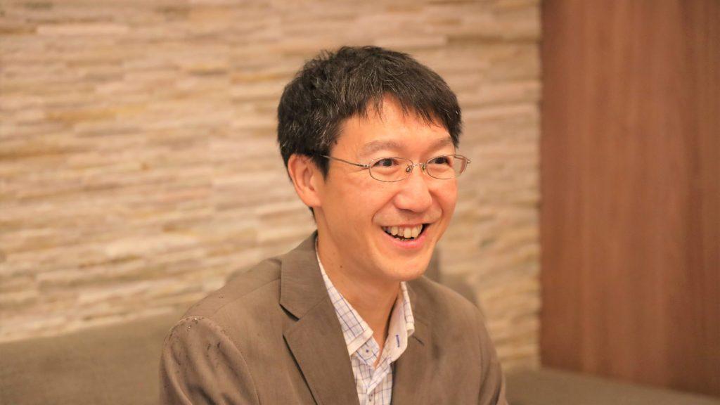 三國さんが笑顔でインタビューを受けている画像。