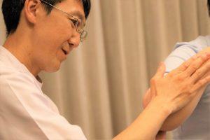 三國さんがマッサージのせじゅつを行い、患者さんの腕にテーピングを貼っている画像。