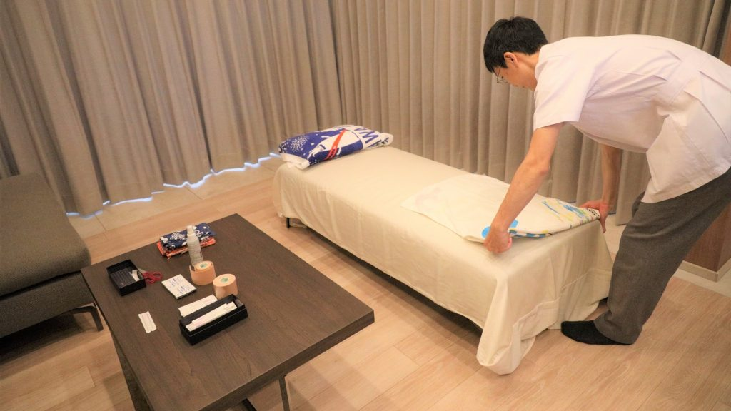三國さんがマッサージ室の施術台を整えている画像。