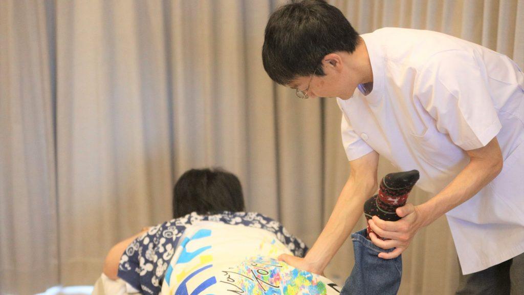 三國さんがマッサージ室で患者さんにせじゅつしている画像。