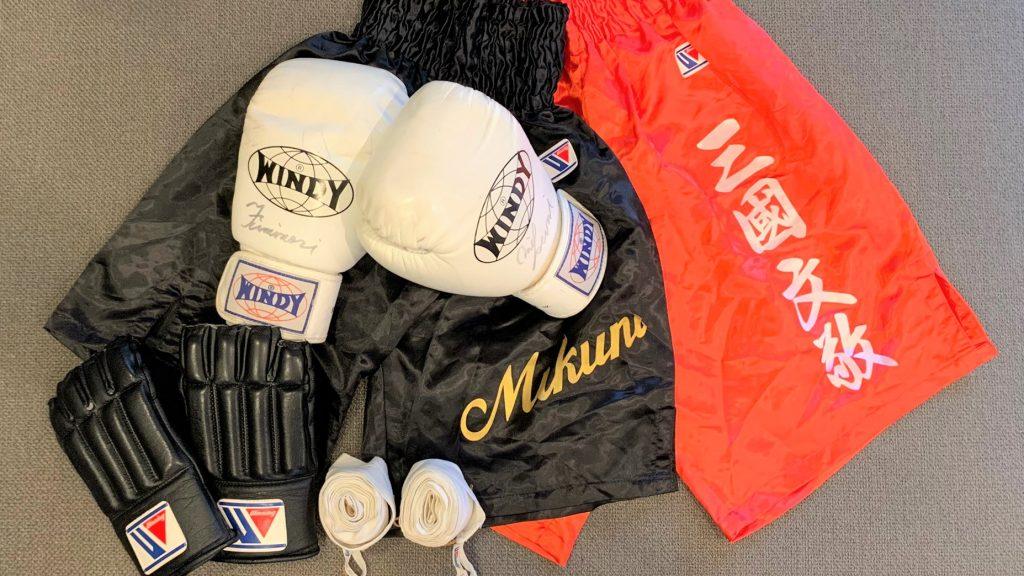ボクシンググローブや名前の入ったボクシングパンツを並べて撮影した画像。