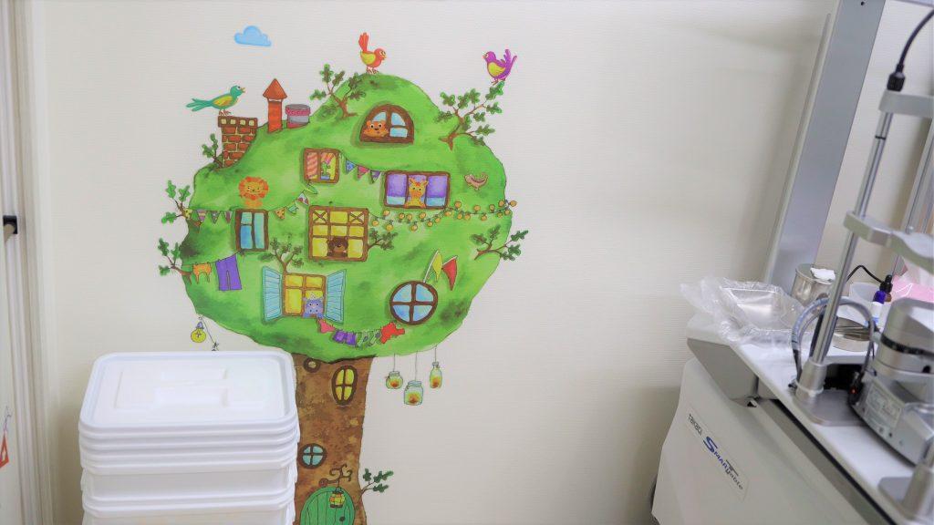 診察室の壁にあるかわいい木のイラストを撮影した画像。