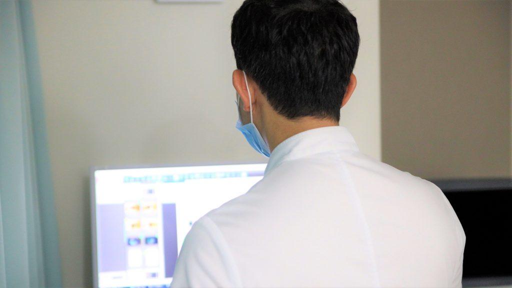 パソコンで診察結果を見る翁長先生を背後から撮影した画像。