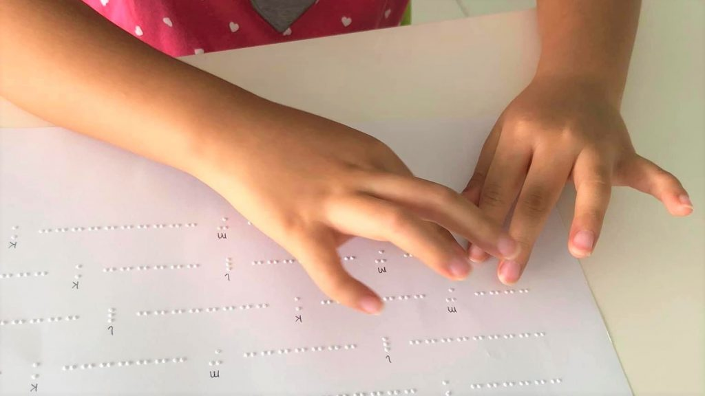 アルファベットの点字を触読する娘さんの手元の画像