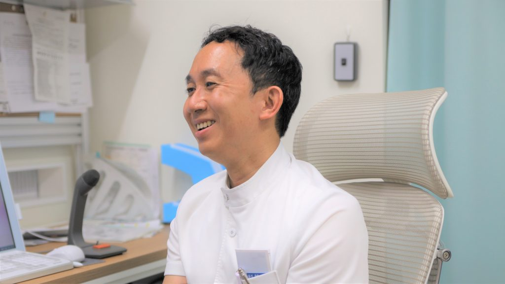 笑顔でインタビューに答える翁長先生の画像。