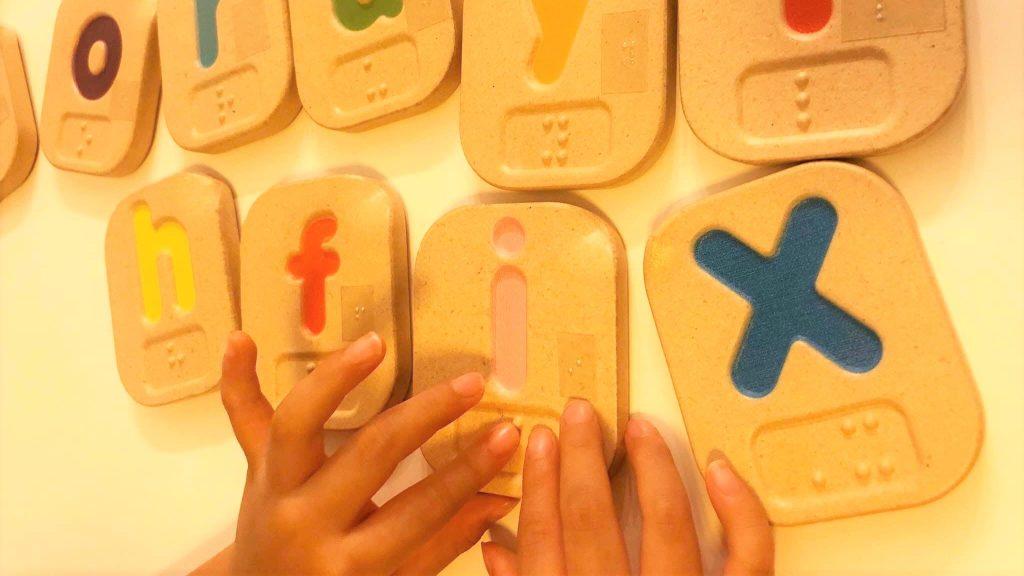 手のひらサイズの模型でアルファベットの形を学習する娘さんの画像。