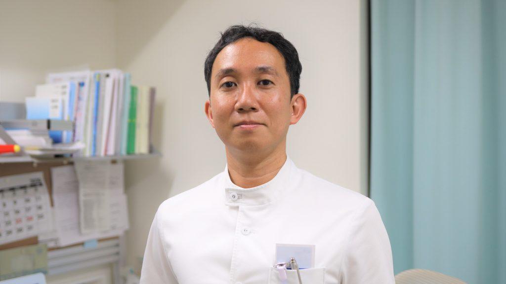 診察室で立っている翁長先生の上半身を撮影した画像。