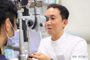 翁長先生が眼科の診察室で機械を使って診察している画像。