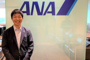 ANAのロゴの前で大澤さんが笑顔で立っている画像。