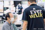 エバーウォークの職員が利用者と話をしている画像。職員の背中にエバーウォークのロゴが入っている。
