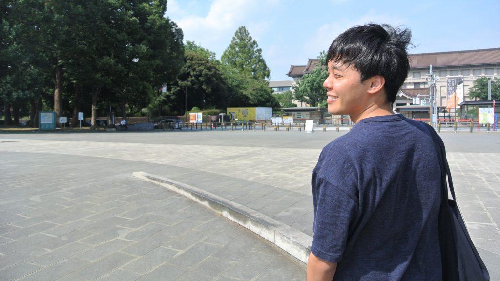 笑顔で歩く三輪さんを斜め後ろから撮影した画像。