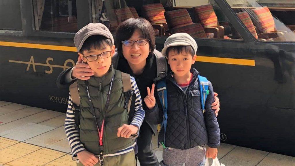 佳子さんとお子さん2人が電車の前で記念撮影している画像。