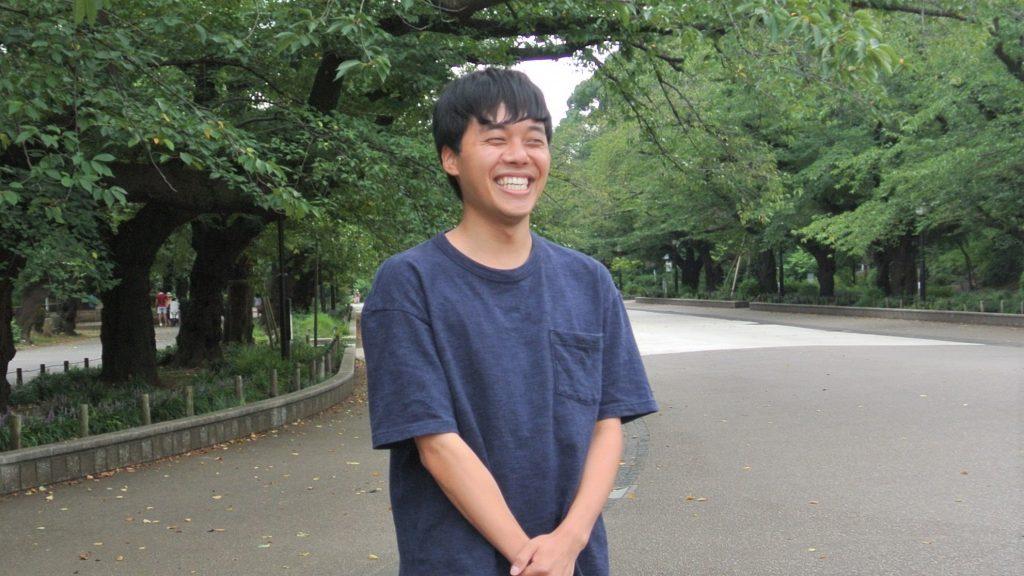 三輪さんが公園で笑顔で立っている画像。