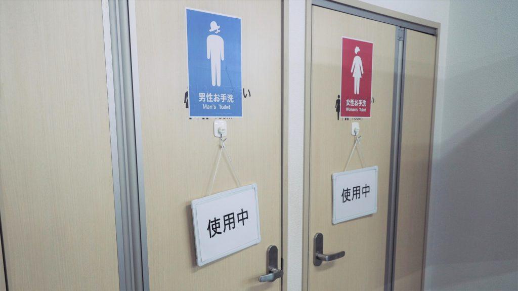 トイレの入り口の画像。空き状況を示すボードがぶら下げられている。
