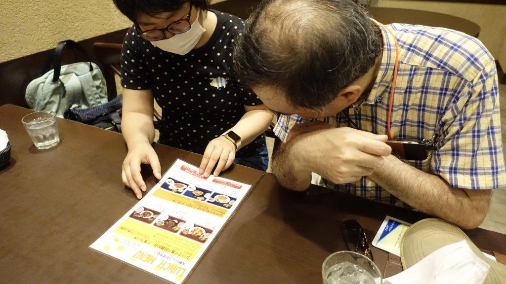 下田さんが鈴木さんに口頭でメニューを説明している画像。