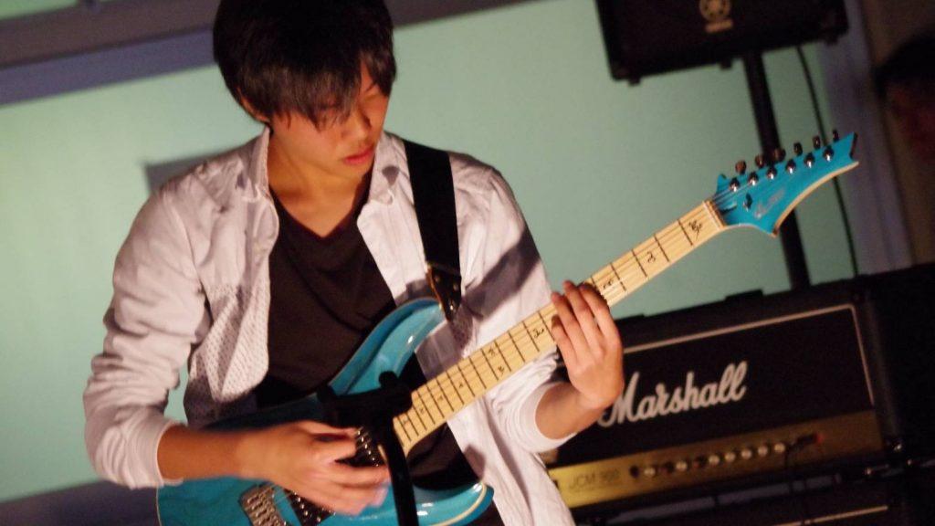 ライブのステージ上で三輪さんが真剣な表情でギターを弾いている画像。