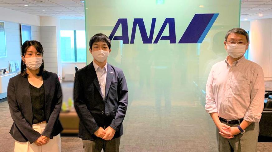 ANAのロゴの前で、大澤さん、黒岩さん、石井さんが立っている画像。