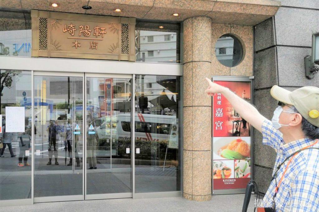 鈴木さんが崎陽軒のお店の前で、入口を指さしている画像。